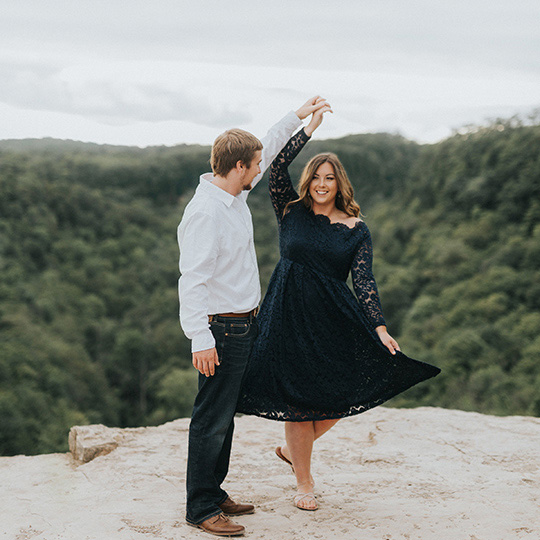 Engaged couple dancing on top of the mountain
