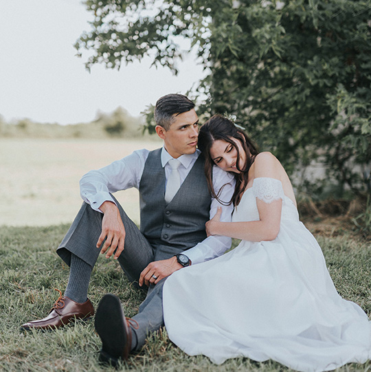 Wedding couple sitting in the field