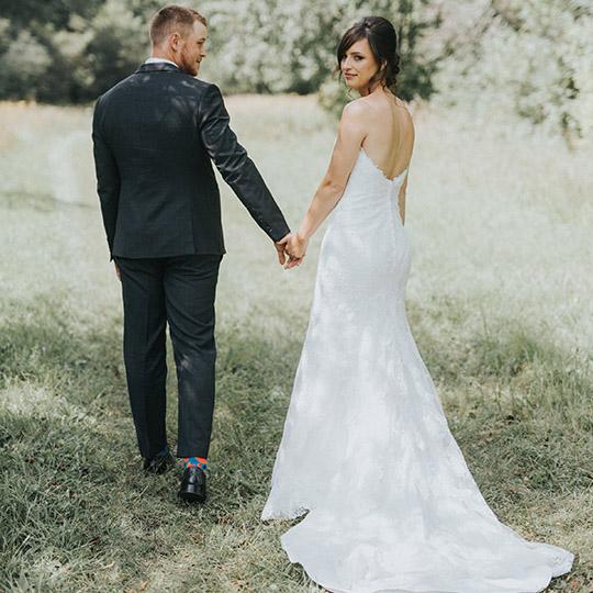 Bride and groom walking in the field